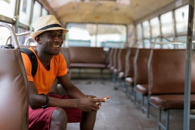 Przemyślany młody szczęśliwy turysta uśmiecha się i trzyma telefon komórkowy podczas jazdy autobusem w bangkoku w tajlandii