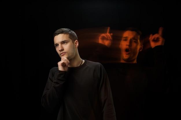 Przemyślany na zewnątrz, inspirowany wewnątrz. wszechstronność człowieka - otwarte emocje i ukryte uczucia. kaukaski mężczyzna na czarnej ścianie z różnymi twarzami stanu. podwójna ekspozycja. zdrowie psychiczne.