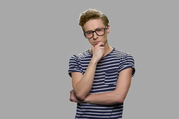 Przemyślany nastoletni chłopak w okularach. zamyślony nastoletni chłopak nerd w okularach maniakiem na szarym tle. poważny wyraz twarzy.