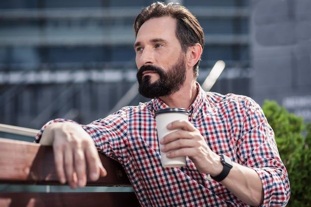 Przemyślany nastrój. skoncentrowany brodaty mężczyzna odpoczywa na świeżym powietrzu podczas picia kawy