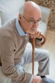 Przemyślany nastrój. widok z góry doświadczonego, odnoszącego sukcesy, starszego mężczyzny, myślącego, opierając się na lasce i siedząc na kanapie