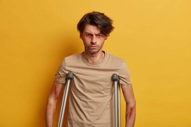 Przemyślany niezadowolony mężczyzna ze siniakami wokół oczu ma obrażenia zagrażające życiu, odczuwa straszny ból, dochodzi do siebie po operacji w domu, odizolowany na żółtej ścianie, cierpi po wypadku drogowym