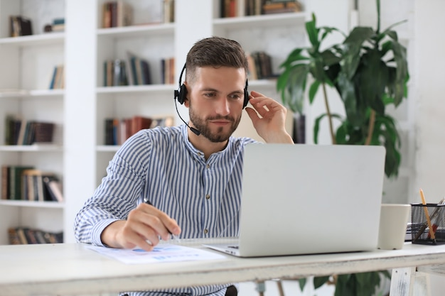 Przemyślany nowoczesny biznes człowiek pracuje za pomocą laptopa siedząc w biurze.