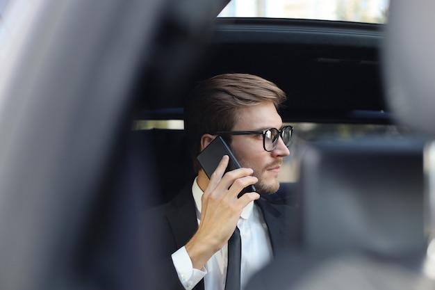 Przemyślany pewnie biznesmen rozmawia przez telefon siedząc w samochodzie.