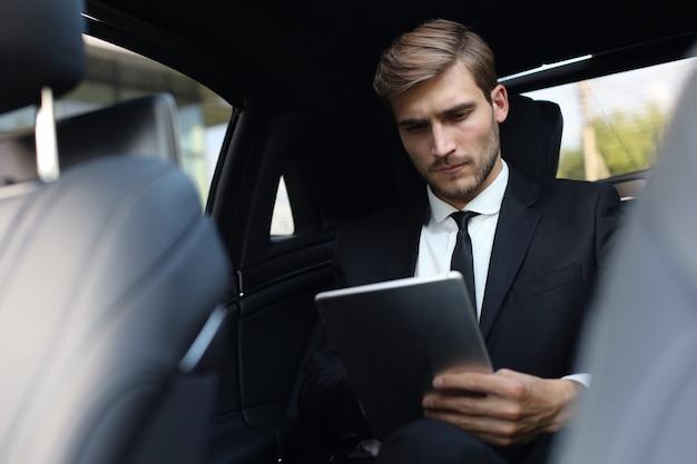 Przemyślany pewnie biznesmen siedzi w luksusowym samochodzie i za pomocą tabletu.