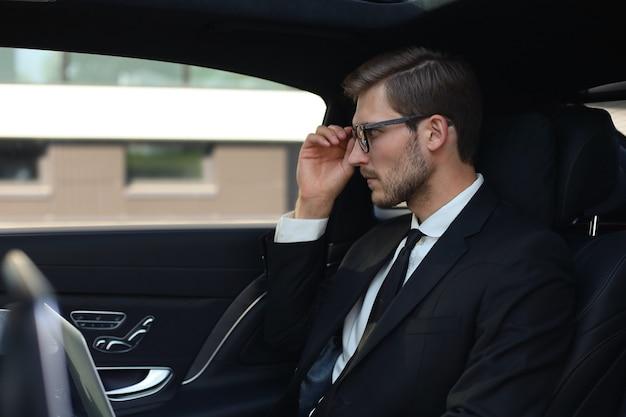 Przemyślany pewnie biznesmen trzymając rękę na okularach siedząc w luksusowym samochodzie.