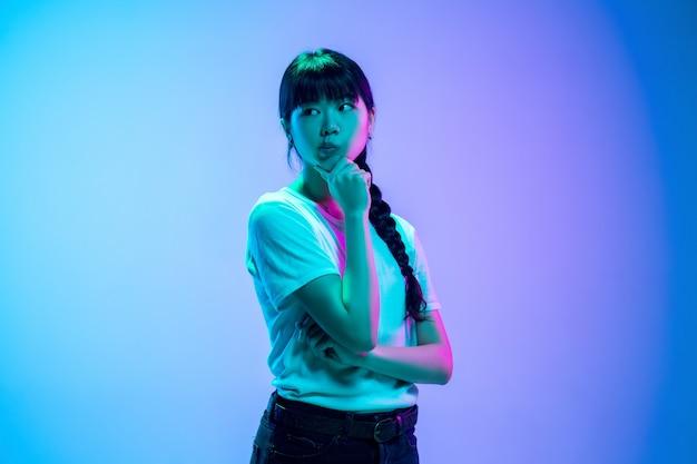 Przemyślany. portret młodej kobiety azjatyckiej na gradientowym niebiesko-fioletowym tle studio w świetle neonowym. pojęcie młodości, ludzkie emocje, wyraz twarzy, sprzedaż, reklama. piękna brunetka modelka.