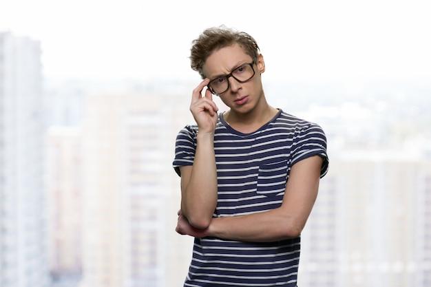 Przemyślany poważny chłopak dotyka jego okularów. zmarszczył nastoletni chłopak w pasiastym t-shircie. na białym tle.