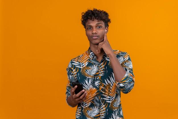 Przemyślany pozytywny młody przystojny ciemnoskóry mężczyzna z kręconymi włosami w koszuli z nadrukiem liści trzymając telefon komórkowy, patrząc na kamery na pomarańczowym tle
