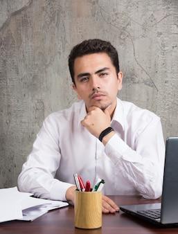 Przemyślany pracownik z kartkami i siedzący przy biurku. wysokiej jakości zdjęcie
