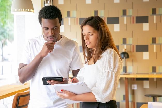Przemyślany projektant omawiający nowy projekt z klientem i robiąc notatki