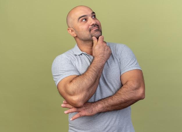 Przemyślany, przypadkowy mężczyzna w średnim wieku, patrzący na bok, trzymający rękę na brodzie, odizolowany na oliwkowozielonej ścianie