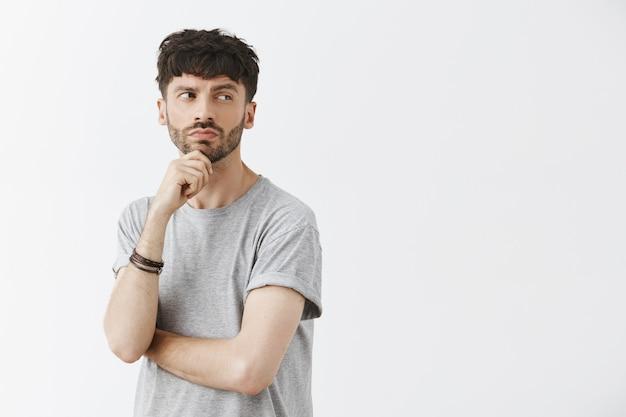 Przemyślany przystojny facet pozuje przy białej ścianie