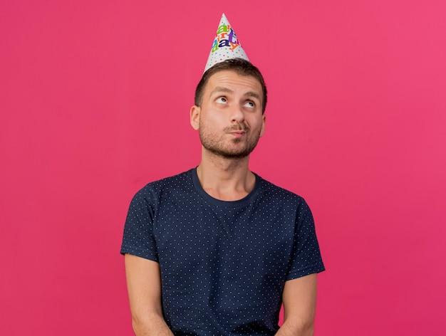 Przemyślany przystojny kaukaski mężczyzna ubrany w czapkę urodzinową patrzy w górę na białym tle na różowym tle z miejsca na kopię