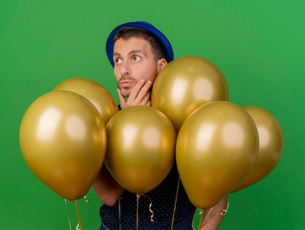 Przemyślany przystojny mężczyzna ubrany w niebieski kapelusz imprezowy kładzie rękę na podbródku stojaki z balonami z helem patrząc z boku na białym tle na zielonej ścianie z miejscem na kopię
