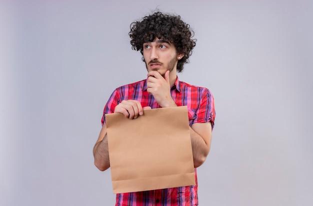 Przemyślany przystojny mężczyzna z kręconymi włosami w koszuli w kratę, trzymając torbę na zakupy, patrząc z boku