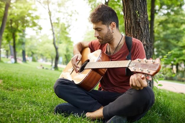 Przemyślany przystojny młody człowiek gra na gitarze w parku, opierając się na drzewie i siedząc na trawie