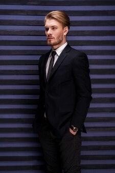 Przemyślany przystojny. widok z boku przystojnego młodego mężczyzny w formalwear, trzymającego się za ręce w kieszeniach i odwracającego wzrok, stojąc na tle pasiastych