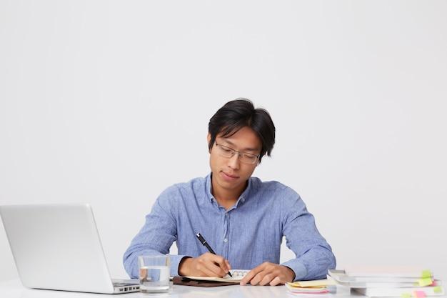 Przemyślany skoncentrowany azjatycki młody biznesmen w okularach, pracujący przy stole z laptopem i plan pisania w notatniku na białej ścianie