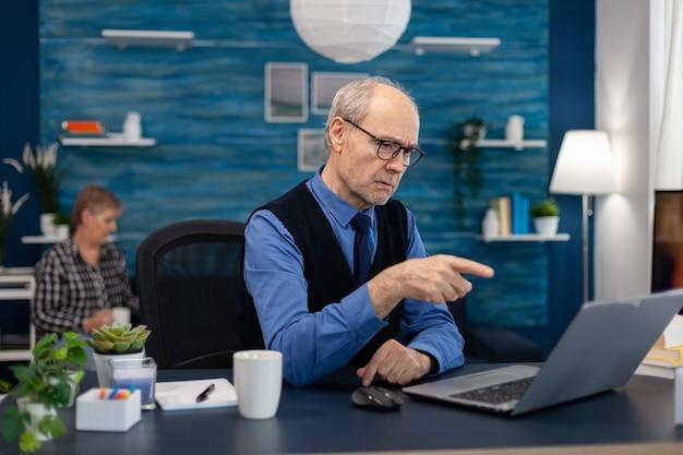 Przemyślany starszy biznesmen wskazujący na laptopa podczas pracy w domu starszy mężczyzna przedsiębiorca ...
