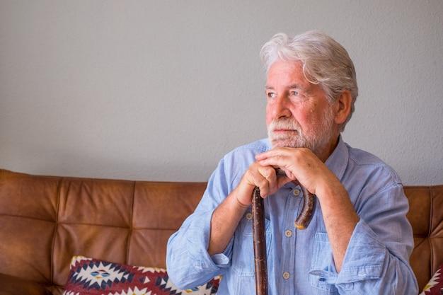 Przemyślany starszy mężczyzna opierając się na lasce siedząc na kanapie. samotny starszy mężczyzna siedzi w salonie w domu. staruszek z siwymi włosami oparty na lasce, siedzący na kanapie w domu