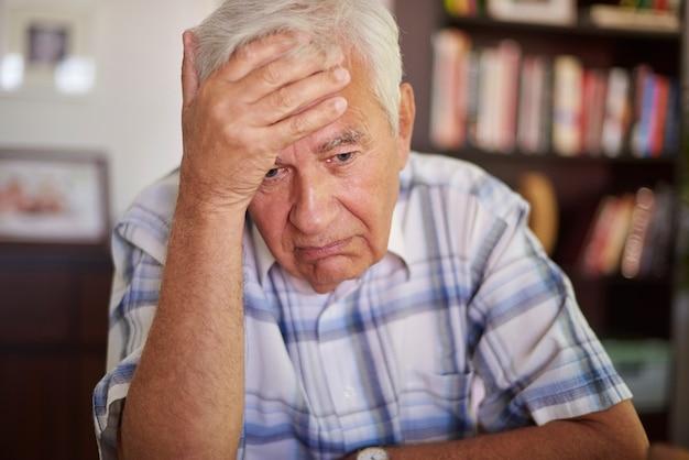 Przemyślany starszy mężczyzna w salonie