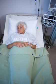 Przemyślany starszy pacjent leżący na łóżku