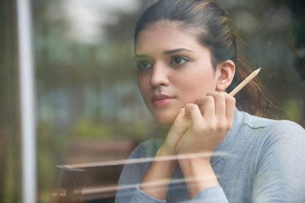 Przemyślany student trzyma ołówek za szkłem