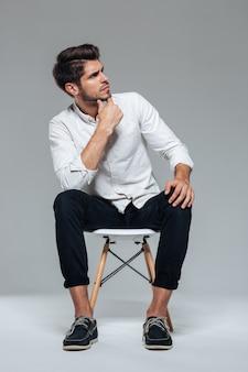 Przemyślany stylowy atrakcyjny dorywczo młody człowiek siedzący na krześle nad szarą ścianą