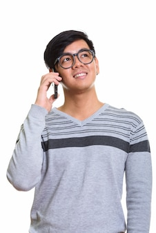 Przemyślany szczęśliwy azjatycki mężczyzna uśmiecha się podczas rozmowy przez telefon komórkowy