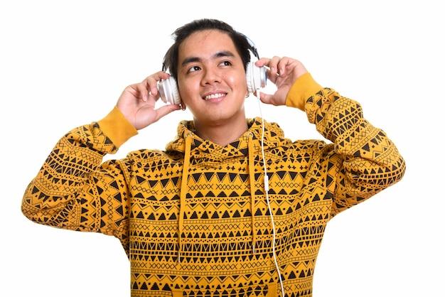 Przemyślany szczęśliwy azjatycki mężczyzna uśmiecha się podczas słuchania muzyki