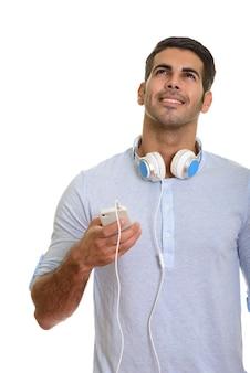 Przemyślany szczęśliwy człowiek perski uśmiecha się i używa telefonu komórkowego podczas noszenia słuchawek