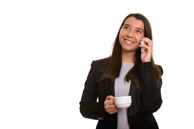 Przemyślany szczęśliwy kaukaski bizneswoman uśmiecha się i rozmawia przez telefon komórkowy, trzymając filiżankę kawy