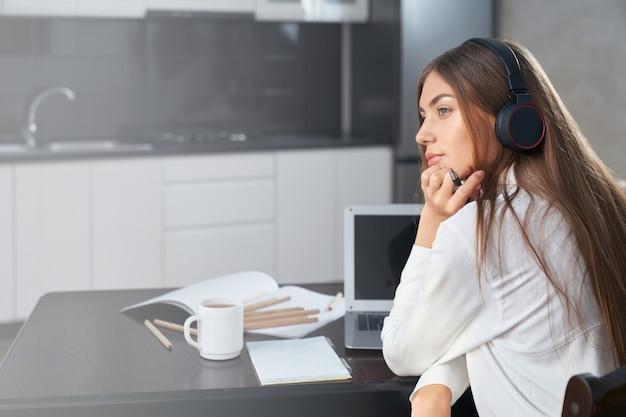 Przemyślany uczeń korzystający z laptopa i słuchawek w edukacji