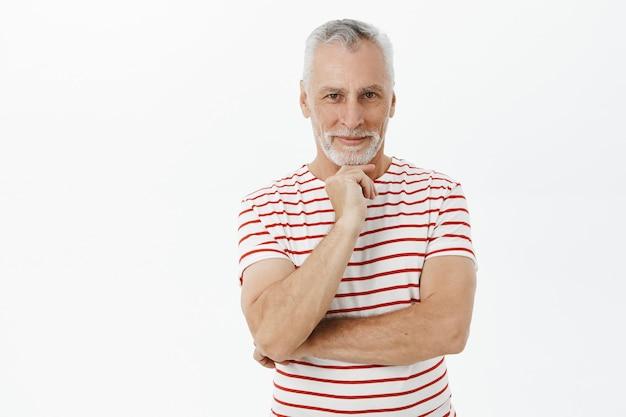 Przemyślany uśmiechnięty starszy mężczyzna w t-shirt patrząc z zadowolonym wyrazem