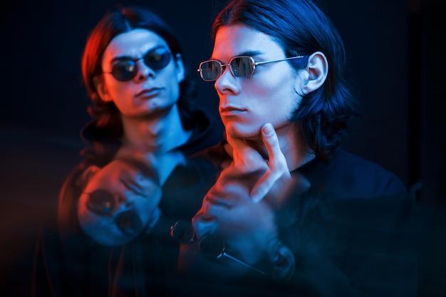 Przemyślany wygląd. portret braci bliźniaków. studio strzałów w ciemnym studio z neonowym światłem
