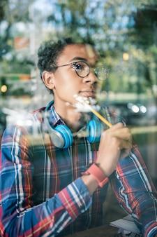 Przemyślany wygląd. przyjemny miły mężczyzna dotykający policzka ołówkiem w poszukiwaniu nowych pomysłów