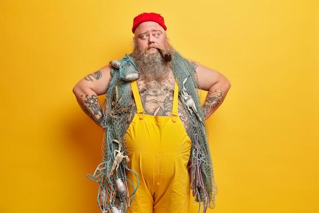 Przemyślny bosman trzyma ręce w pasie, ma gruby brzuch w czerwonym kapeluszu i żółtym kombinezonie, zamyślony, a palący fajki z sieci rybackiej myśli o rejsie morskim. zamyślony rybak