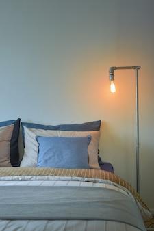 Przemysłowa lampa do czytania i niebieskie poduszki na pościel w nowoczesnym stylu