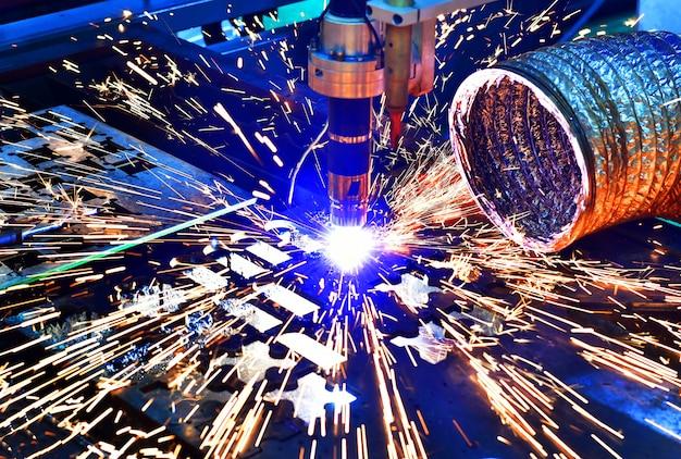 Przemysłowa maszyna do cięcia laserowego podczas cięcia blachy z iskrzącym światłem.