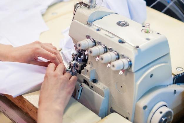 Przemysłowa owerlokowa maszyna do szycia i ręce szwaczki przy pracy w fabryce odzieży