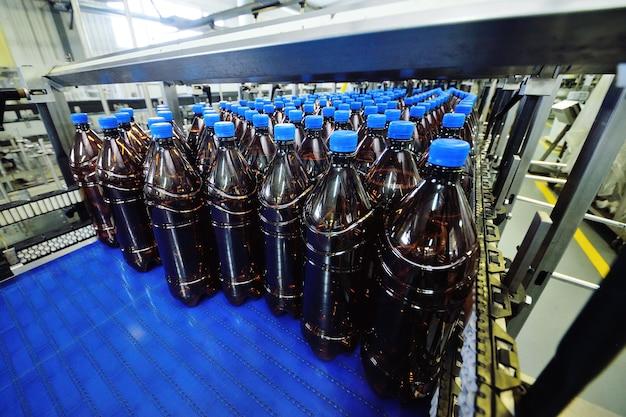 Przemysłowa produkcja napojów gazowanych, piwa, wody. plastikowe butelki pet z napojami lub piwem poruszają się po przenośniku taśmowym w tle fabryki.