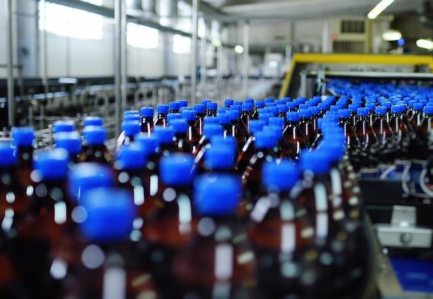 Przemysłowa produkcja spożywcza piwa. plastikowe butelki po piwie na taśmociągu na tle browaru