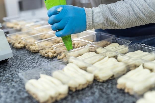 Przemysłowa produkcja żywności. cukiernik robi pyszne desery w fabryce.