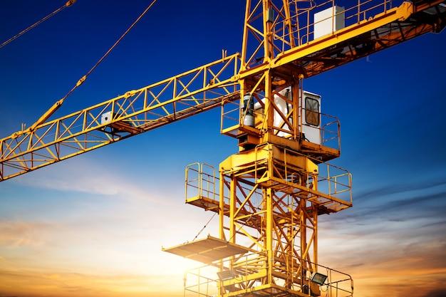 Przemysłowe dźwigi budowlane i sylwetki budynku nad słońcem o wschodzie słońca.