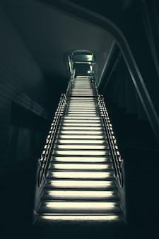 Przemysłowe nowoczesne szare kamienne schody oświetlone światłami prowadzącymi w górę