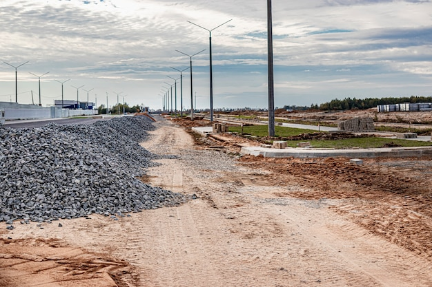 Przemysłowe tło z kupą żwiru. wydobycie żwiru. budowa dróg. stosy żwiru na budowie.