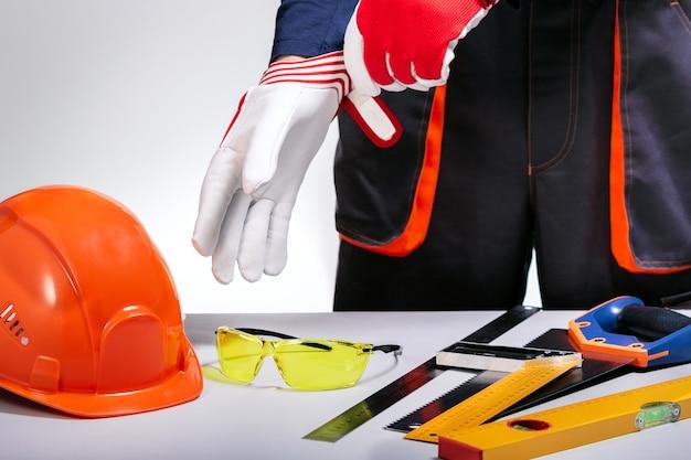 Przemysłowe ubrania ochronne. konstruktor nakłada rękawice ochronne na ręce.