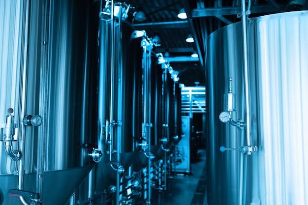 Przemysłowe wnętrze nowoczesnego browaru rzemieślniczego z cylindrycznym metalowym zbiornikiem piwa