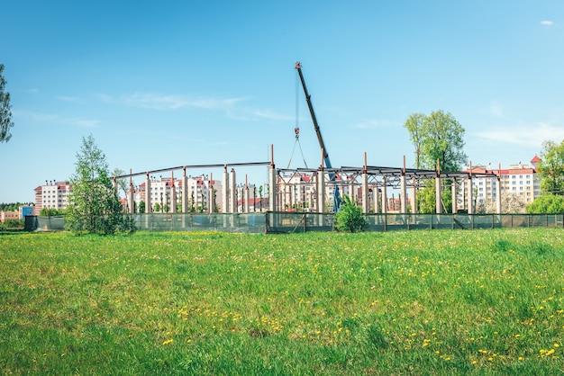 Przemysłowe żurawie wieżowe z niedokończonymi wysokimi budynkami i błękitnym niebem w tle. białoruś.